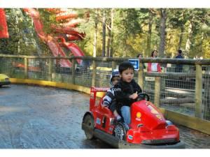 Raed dan Hakim bermain kereta, berlatarbelakangkan water slide di Landmark Park